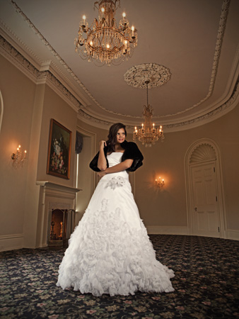 Satin A-line gown with a strapless neckline and full skirt with ruffles and swirls of chiffon and tulle. By Anjolique, $1,625 at Amore Bridal, Dover. Chinchilla fur shrug by Modern Trouseau, $1,050 at Jennifer's Bridal, Hockessin
