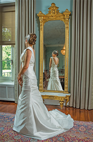 Reflecting This slenderizing mikado A-line by Sottery & Midgley features cap sleeves plunging to a deep V-neck and an empire waist showcased by Swarovski crystals, $1,098; Susan Anne headpiece, $69; both from Brides 2 Be by Hope Mitchell, Lewes