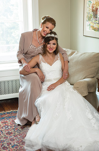 Hi, Mom! The bride's mother dazzles in a formal, two-piece silky crepe suit. The sleeveless dress features cut-out embroidery accented with hand-beading, $519, Lady's Image, Wilmington; freshwater cultured pearl earrings, $180, and pearl necklace with diamond accents, $450, and 1.63-carat diamond with a 14-karat white gold band, $8,690, all from Bellinger's Jewelers, Rehoboth Beach. The bride is wearing a layered, glitter gown by Pronovias with rebrode lace, organza flowers, feathers and gemstone embroidery. The flared skirt features silver gemstone embroidery appliqués at the waist, $2,075, Anastasia's Bridal, Wilmington. Headpiece by Haley Anne, $119, Brides 2 Be by Hope Mitchell, Lewes. Three-stone, 1.84-carat diamond with a 14-karat white gold band, $9,995, Bellinger's Jewelers, Rehoboth Beach