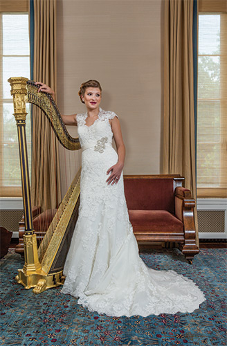 On That Note... This gown by Allure is created from a rich lace appliqué on soft net. The sculpted neckline features scalloped cap sleeves and a keyhole back, $1,663, Claire's Fashions, Wilmington; 1.84-carat, three-stone diamond with a 14-karat white gold band, $9,995, and freshwater cultured pearl button earrings, $180, both from Bellinger's Jewelers, Rehoboth Beach