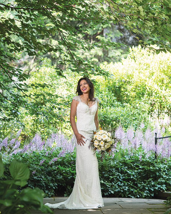 Brandy gown by Maggie Sottero,  Haute Couture Collection, $1,598, from  Brides 2 Be by Hope Mitchell, Lewes, Del.  Gregg Ruth diamond teardrop necklace,  $8,000, and Gregg Ruth diamond dangle  earrings, $6,500, all from A.R. Morris Jewelers,  Wilmington and Greenville, Del.  A bouquet of roses, hypericum,  agonis, magnolia leaves and thistle by  Petah Bashano Event & Floral Design.