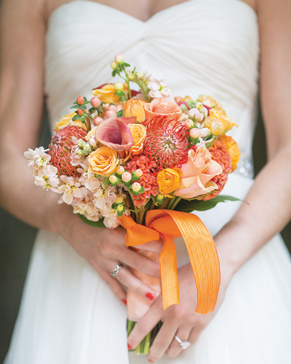 A bouquet of roses, ranunculus, stock, mini calla lilies, spray roses, cocks comb, hypericum berries and pincushion protea, from Bloomsberry Flowers.