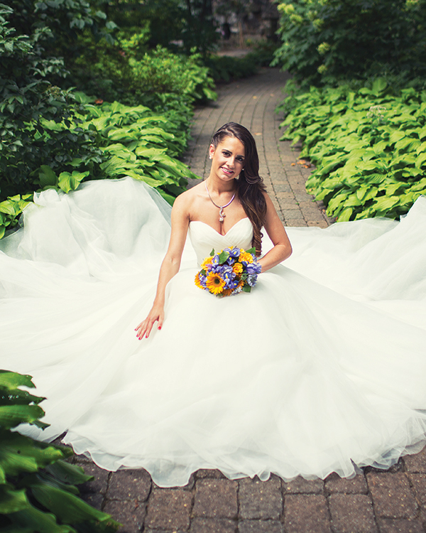 Allure gown, $989, from  Brides 2 Be by Hope Mitchell.  Omega chain necklace, $3,800,  and freshwater pearl slider, $5,670, both from Sayers Jewelers and Gemologists, Smyrna, Del.  A bouquet of iris, mini-sunflowers, roses and scabiosa by Bloomsberry Flowers.