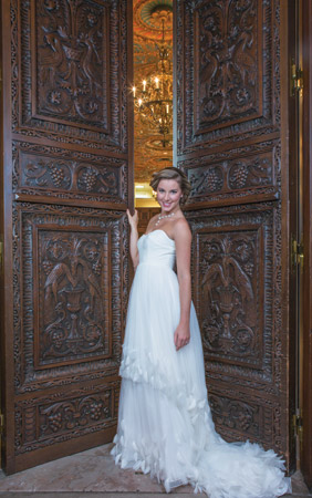 The Calais by San Patrick recalls Hellenic style with its minimalist high-waisted design. Sofia gauze, satin and silk drape perfectly. Appliqués of flower petals, silver and gemstones add just the right touch. $1,272, at Fantasia Bridal, Wilmington; Choker of gold, rhinestones and pearls, $169, at Lady's Image, Wilmington; Ring from Bellinger's Jewelers, Rehoboth Beach.