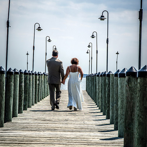 The couple takes a romantic stroll on a pier.