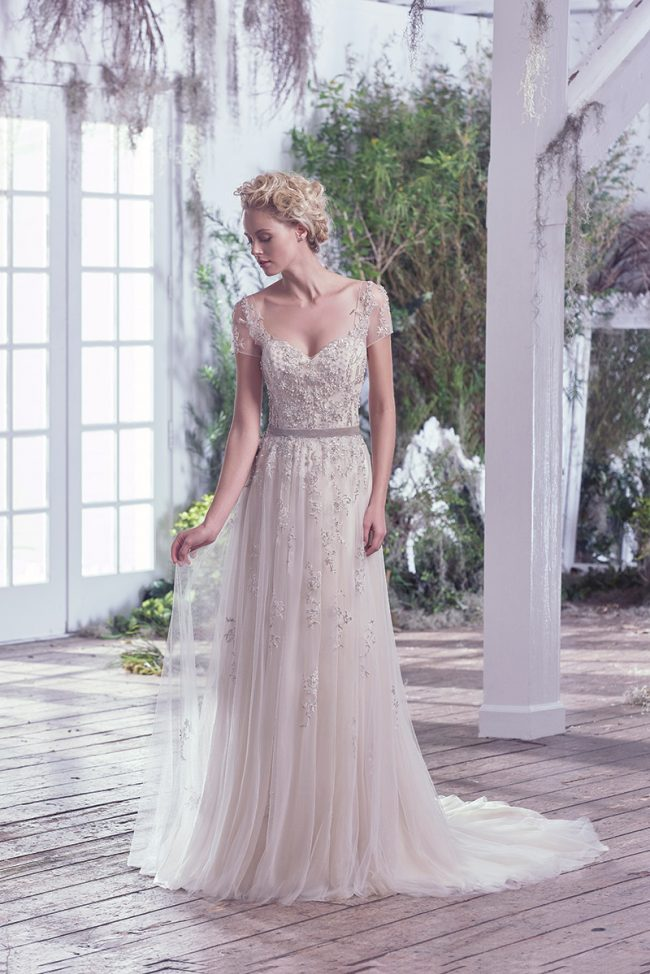 Maggie Sottero Kylie: Ethereal elegance is found in this weightless tulle and metallic embroidered lace sheath wedding dress. Swarovski crystals and beading accent the sweetheart neckline, adding whimsy and romance. Precise detailing delicately adorns illusion lace short sleeves and back. $1,699 at Brides 2 Be By Hope Mitchell.