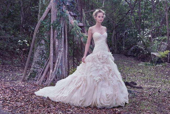 Maggie Sottero Penny: An asymmetrically pleated bodice provides a slim fit through the hips before meeting the grand, swirling tulle and Vincenza organza skirt of this wedding gown. $1,198 at Brides 2 Be By Hope Mitchell.