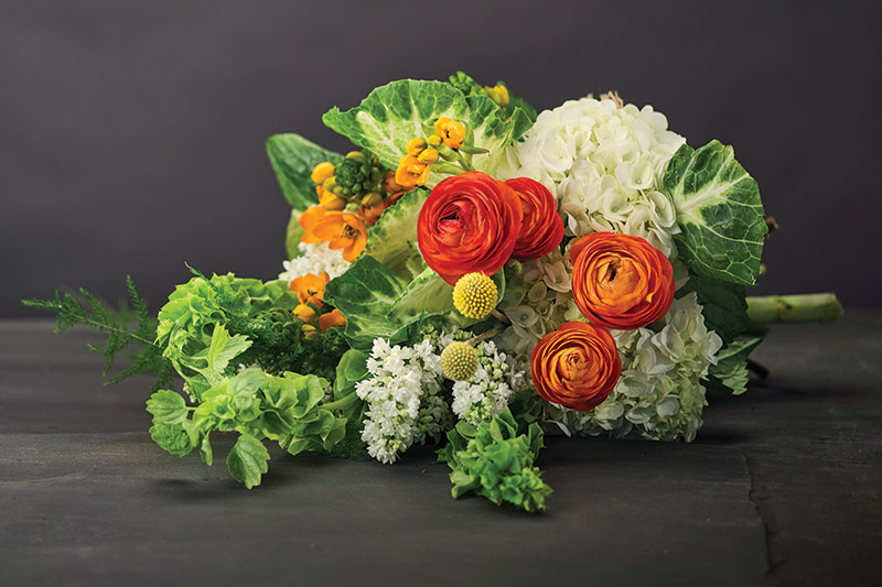 Jen-Mor Florist, Dover, jenmor.com: White ornamental cabbage, star of Bethlehem, orange ranunculus, white French lilac, bells of Ireland, craspedia, asparagus plumosa and white hydrangea.