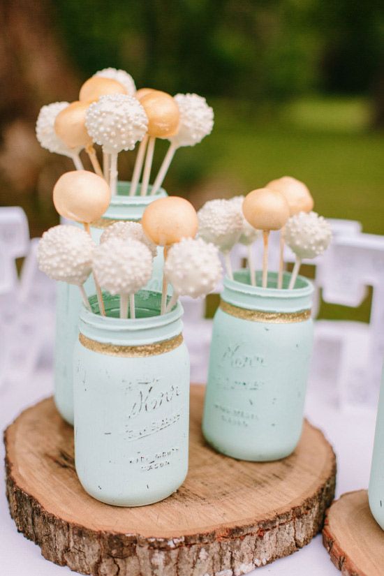 <strong>Wedding Cake Pops</strong> Wedding cake pops add a playful twist to the traditional wedding cake. Plus, they come in a variety of flavors and can be decorated in many ways. This ranch themed wedding used mason jars to hold the cake pops and each of the flower bouquets at every table.