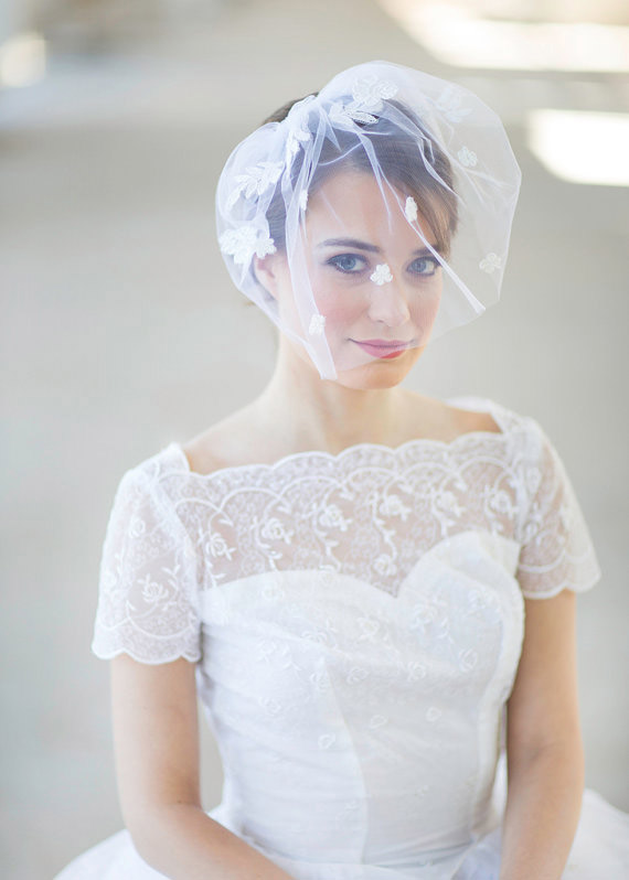 Classic and modern brides alike are embracing the blusher, which kisses the cheeks, like the name suggests. They frame the face in soft tulle and are attached to the crown of the head with a comb, perfect for pairing with an up-do, like this one from JoyandFelicity.