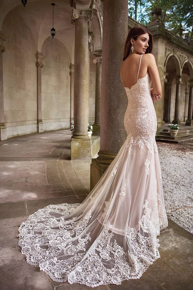 """(David Tutera for Mon Cheri Style Kula) This gown amazes in lace, layered over tulle and satin, finished with a plunge Queen Anne neckline. Fitted through the hips, the bottom flares to a chapel train, revealing the satin layer beneath.  $1,280, <a href=""""www.brides2bebyhope.com"""">Brides 2 Be by Hope Mitchell</a>, Rehoboth, Del."""