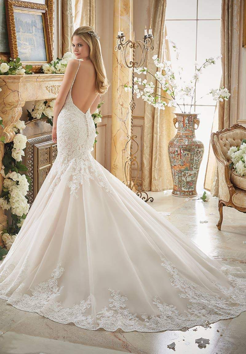 (Mori Lee Bridal Style 2871) Alencon lace appliques embellish the sleeveless dropped waist bodice of this fit-and-flare, tulle gown with chapel train. Beaded spaghetti straps lead into the scalloped V-back with covered button closures.  $1,249, The Dress Matters, Media, Pa., www.thedressmatters.com.