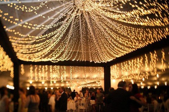 <strong>Canopy of lights</strong> If your venue is a barn or has a high ceiling of wood beams, drape lights around the structure for an ethereal, romantic ambiance.