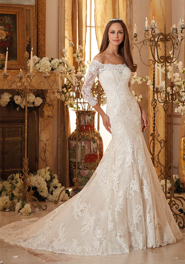 Mori Lee Bridal Style 5477 | Off-the-shoulder wedding dress with three-quarter length illusion sleeves and a scalloped illusion neckline on the sweetheart bodice. Fit-and-flare silhouette is accented with covered buttons and the skirt and chapel train finish in a scalloped lace border hemline. $950, The Dress Matters, Media, Pa., www.thedressmatters.com