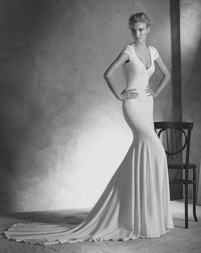 (Atelier Pronovias Style Irune) Silk crepe sheath with beaded sleeves, plunging V-back with covered buttons. $3,170, Jennifer's Bridal, Hockessin, Del., jennifersbridal.com