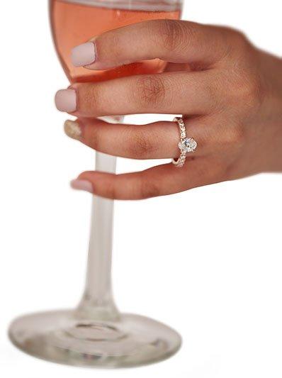 One-carat oval, brilliant-cut diamond surrounded by six, round brilliant-cut diamond prongs on each side. Set in 14-karat rose gold. $8,500,  by Cozzi Jewelers,  www.cozzijewelers.com. Polish: OPI Don't Bossa Nova Me Around; accent nail in Kiara Sky, N521 Sunset Blvd.
