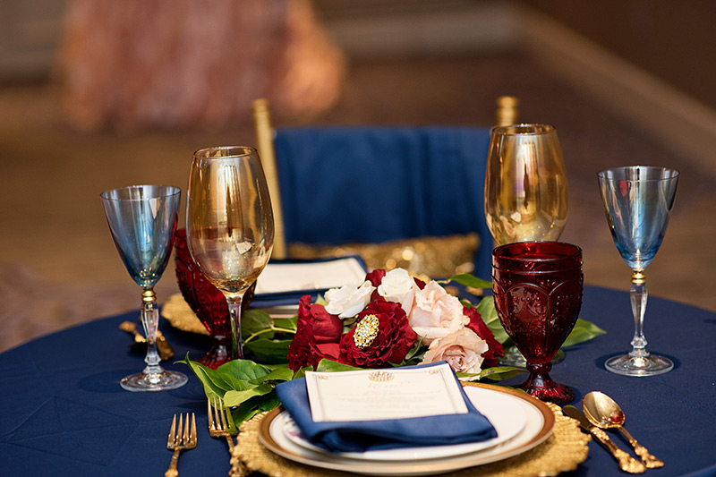 Red and navy wedding reception plate setting.
